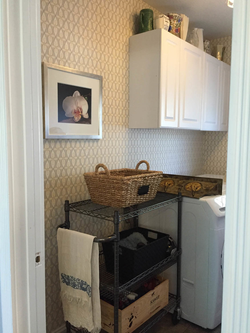 Finished wallpapered laundry room with washer and dryer installed