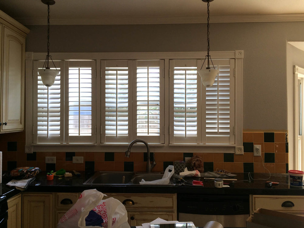 White wood shutters over kitchen sink