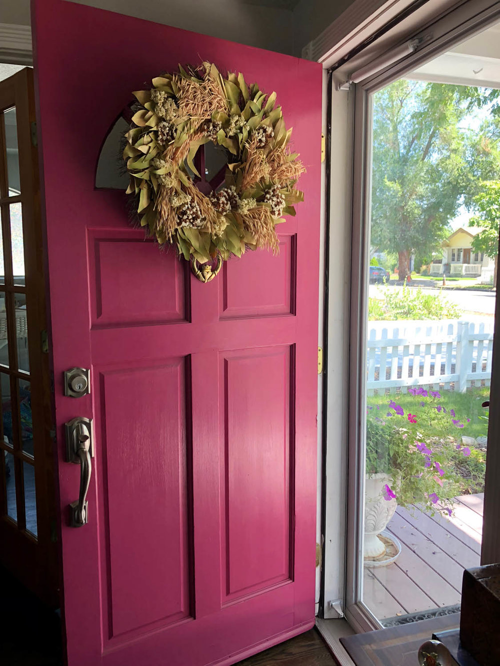 Front door of home painted pink with wreath hanging