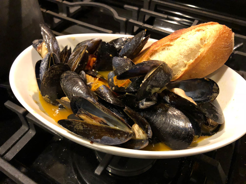 Mussels in dish served with crusty bread.