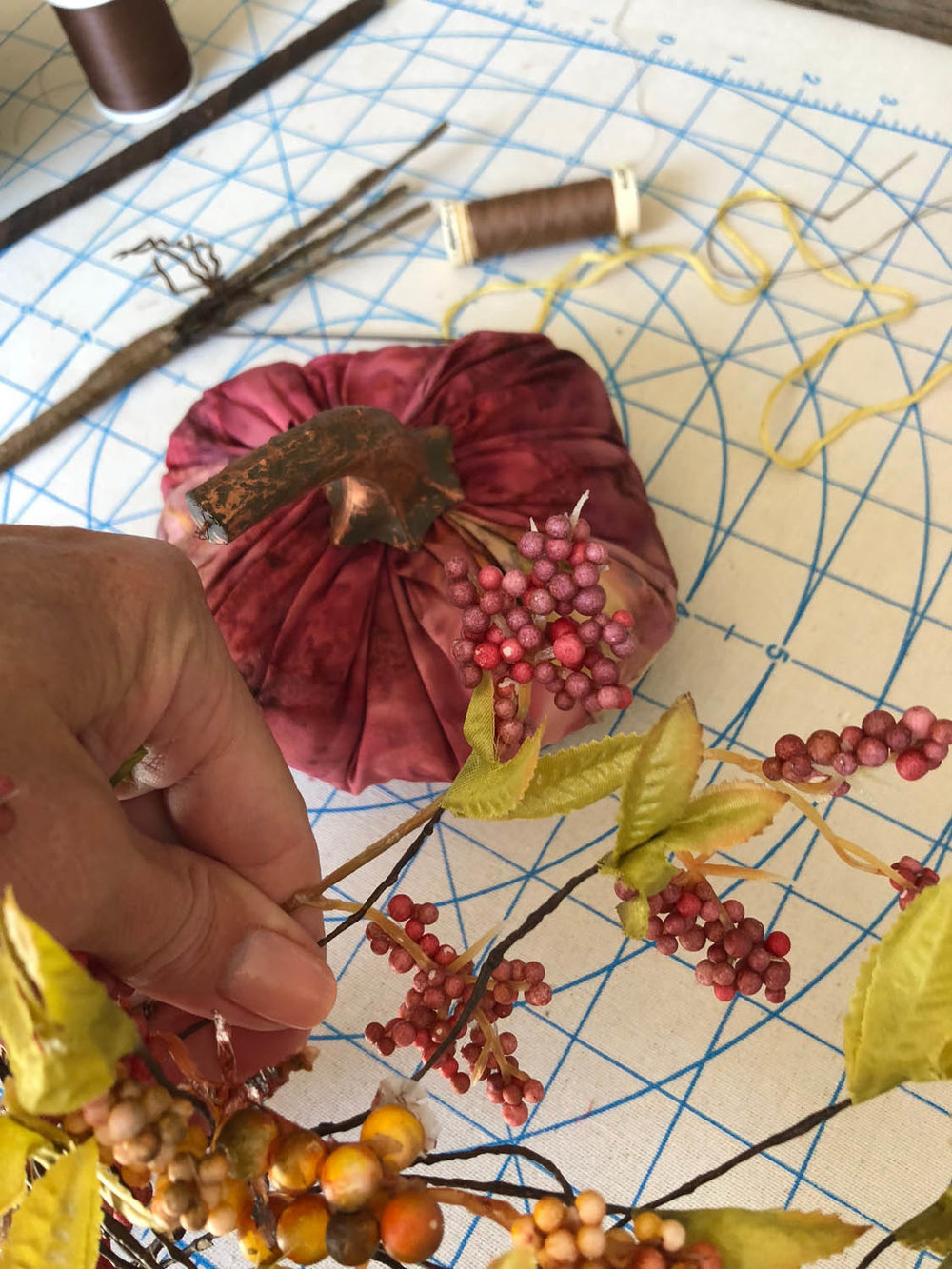 hot glueing stem and fall embellishments to fabric pumpkins