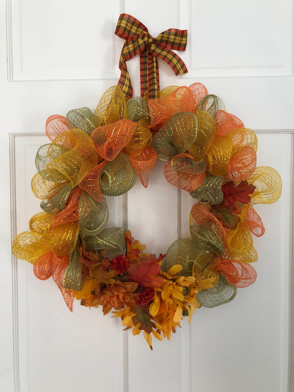 Wire ribbon wrapped on a metal wire frame wreath form base.
