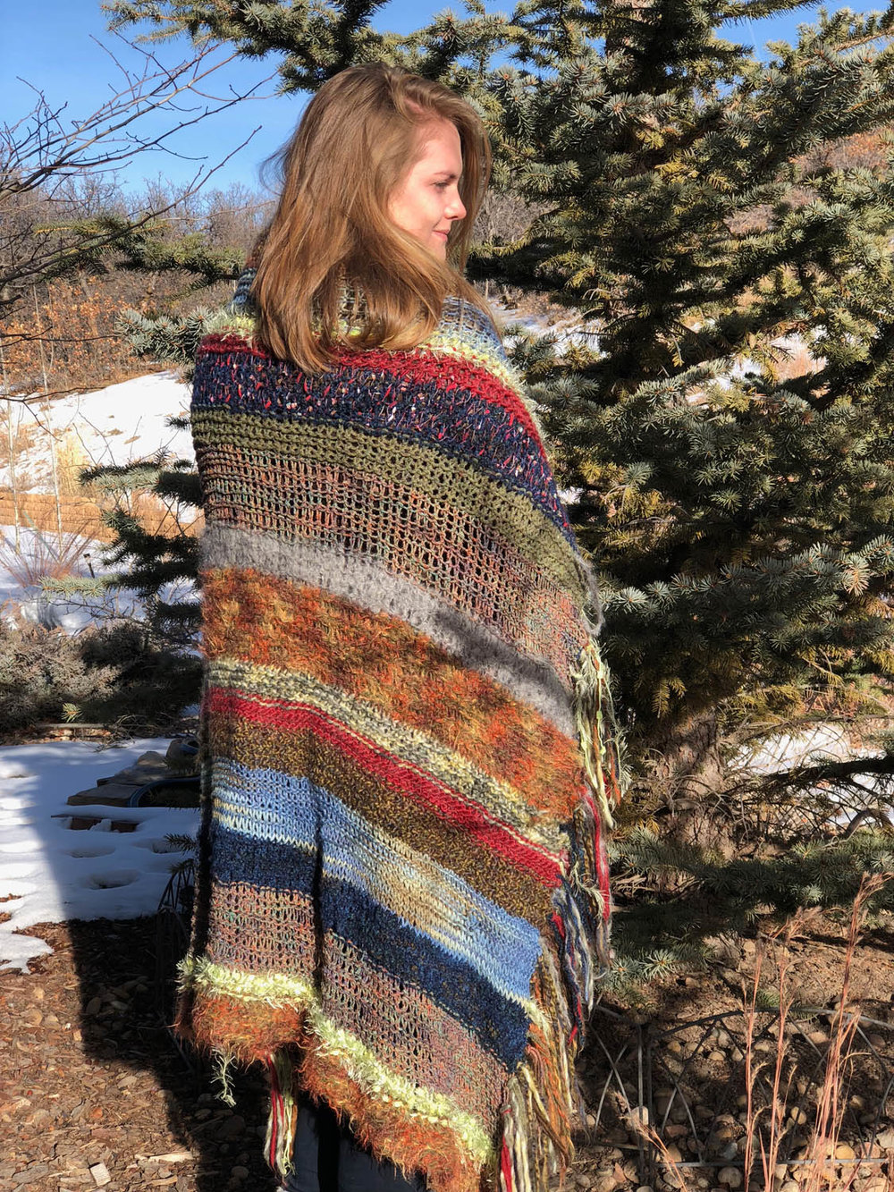 Model wearing scrap-yarn knitted throw as a shawl outside by pine tree in snow.