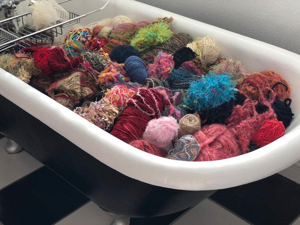 multicolor balls of yarn stored in claw foot vintage bath tub