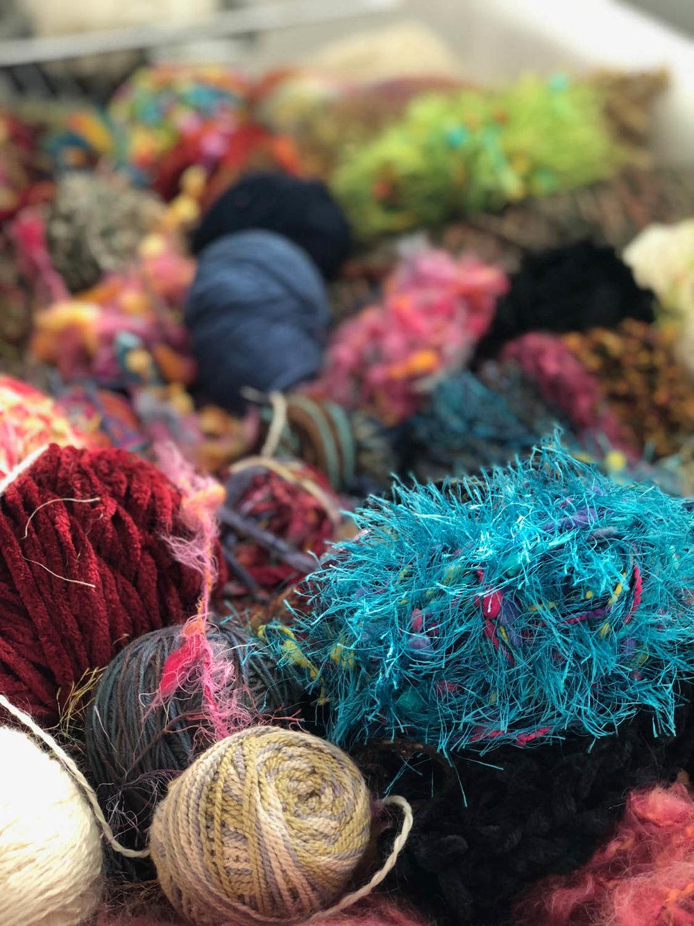 assorted balls of yarn displayed in claw-foot bath tub