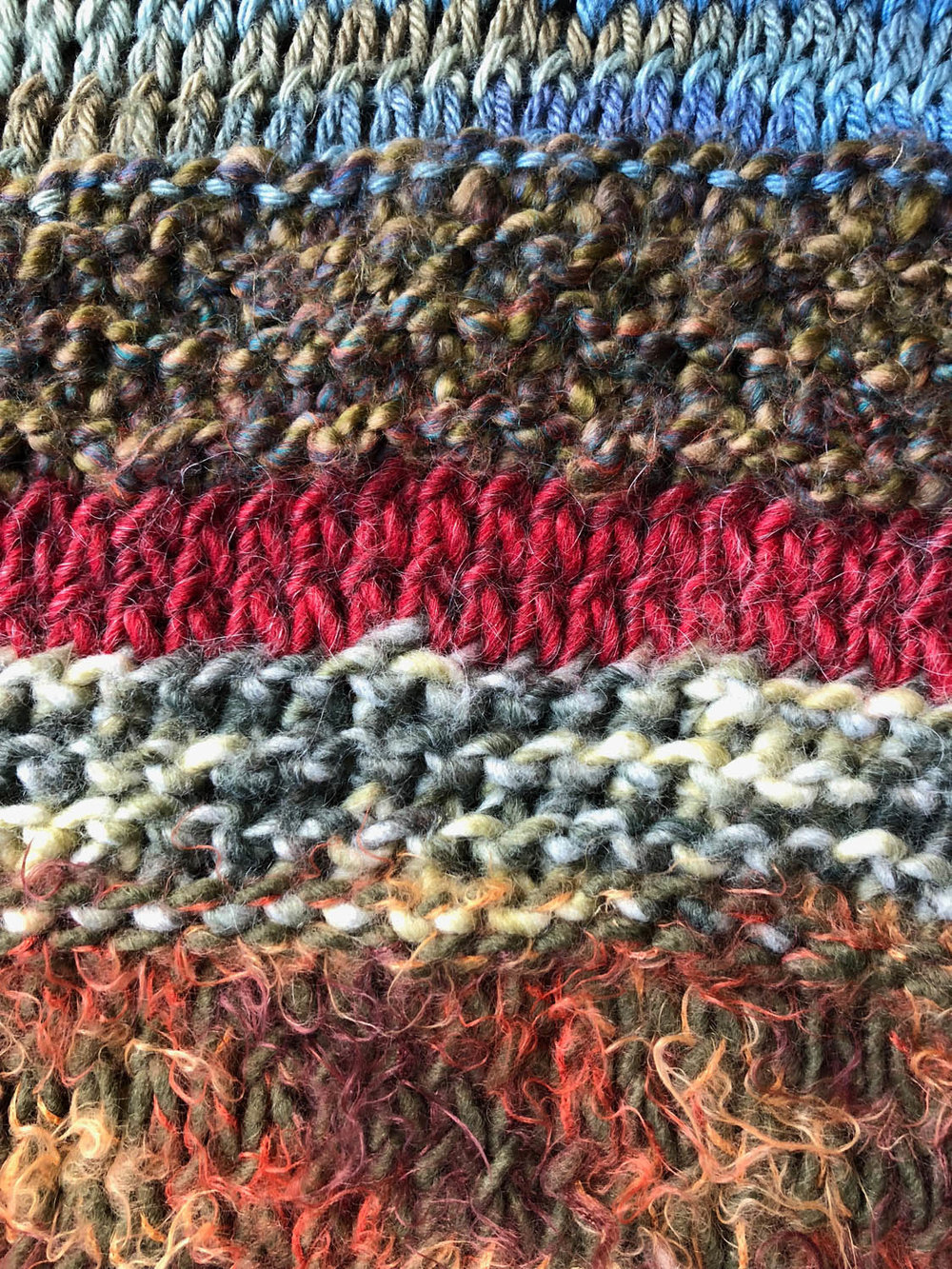 close up of knitted stitches in scrap yarn throw pattern