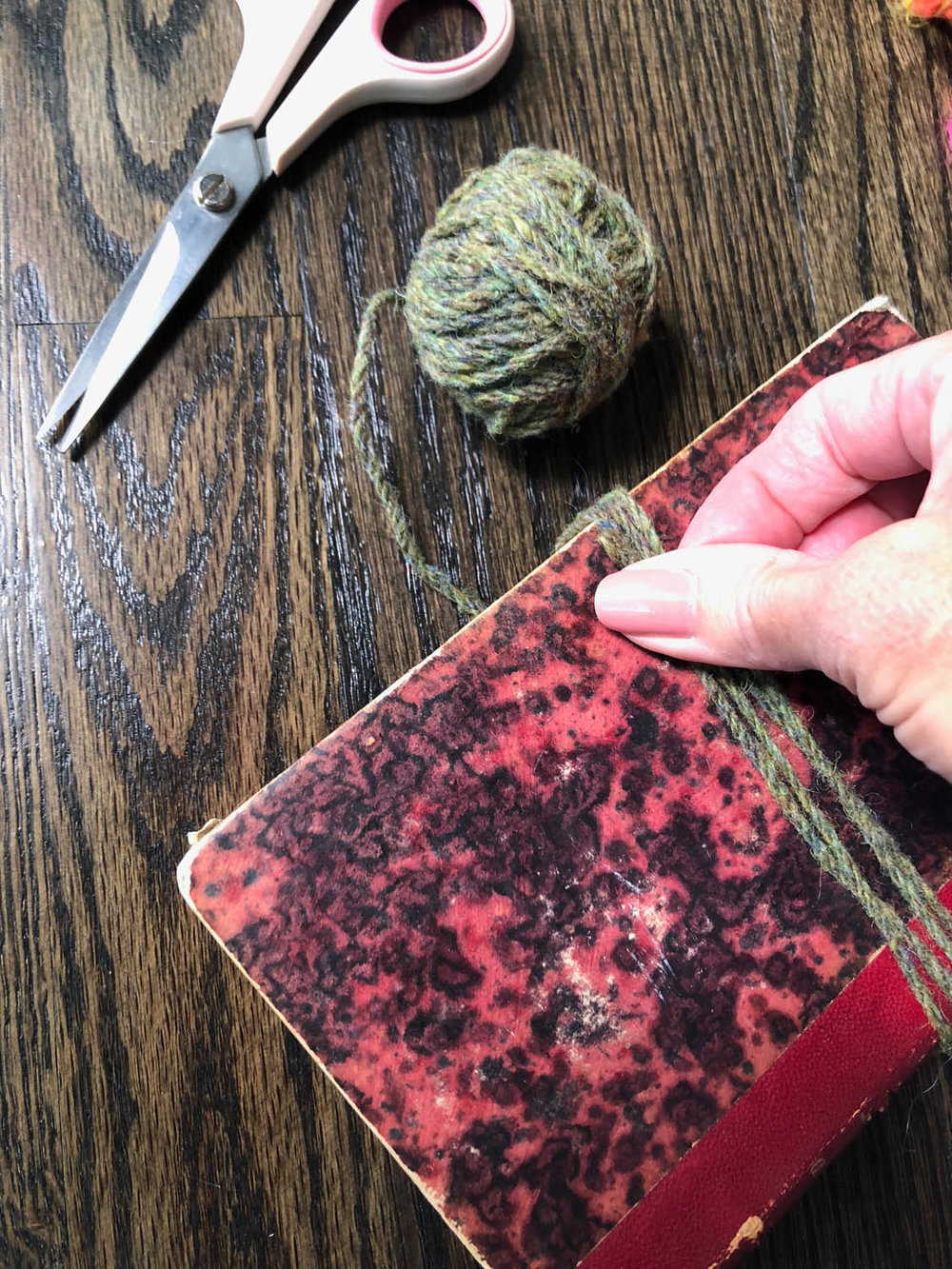 wrapping yarn around book for tassel guide