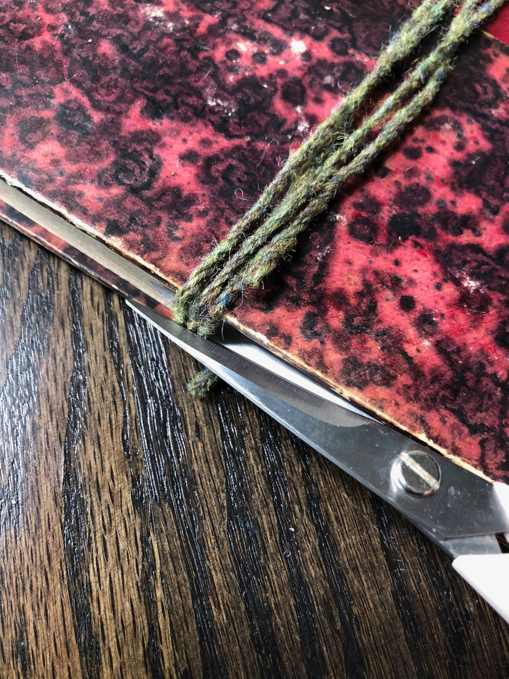 trimming yarn wrapped around book as a tassel guide