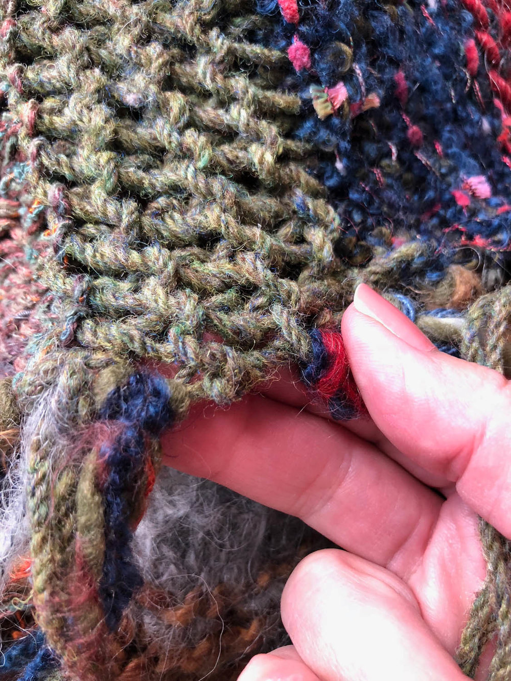 looping group of short yarn through throw for tassel