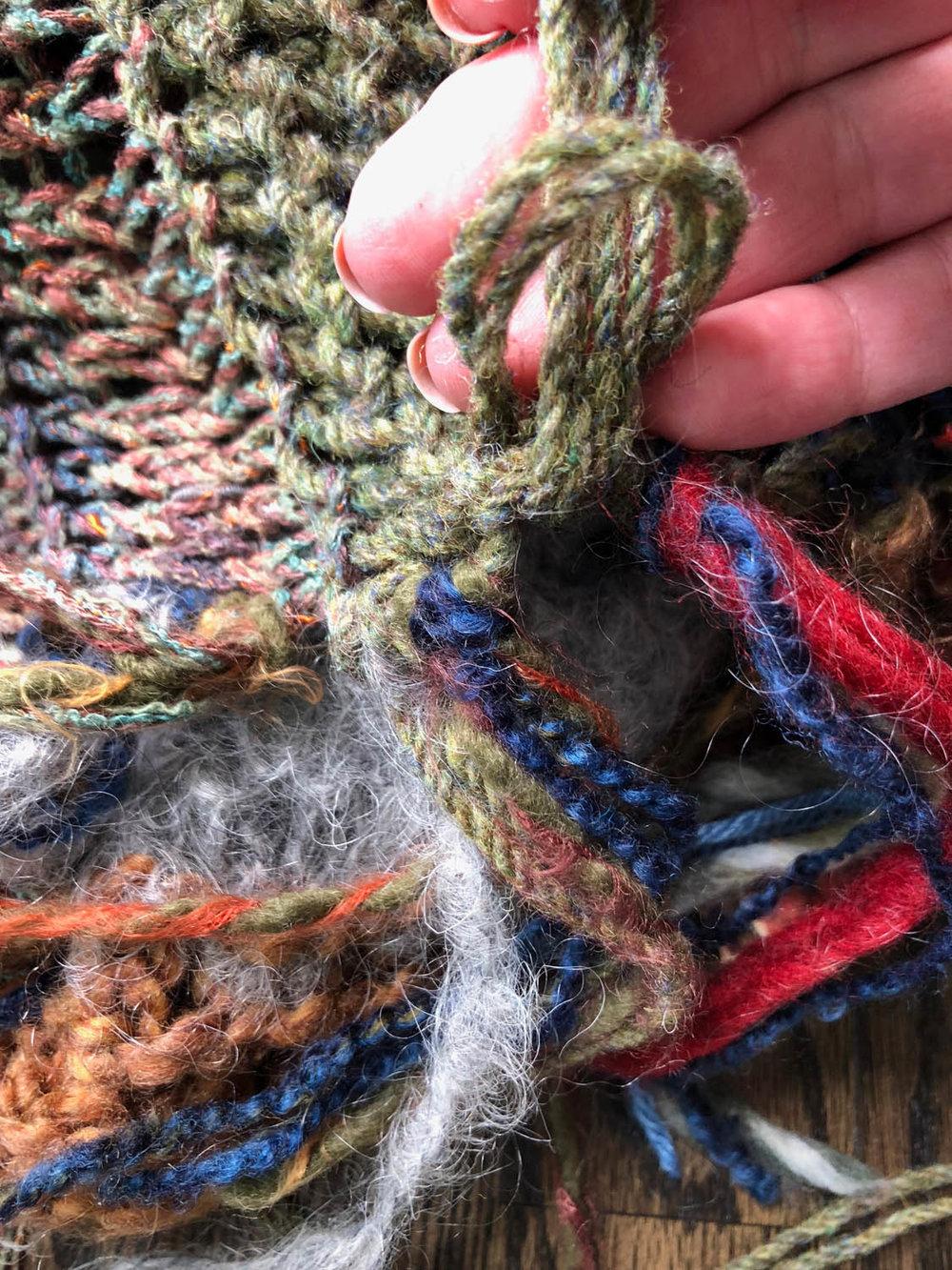 pulling ends of yarn through loop for tassel