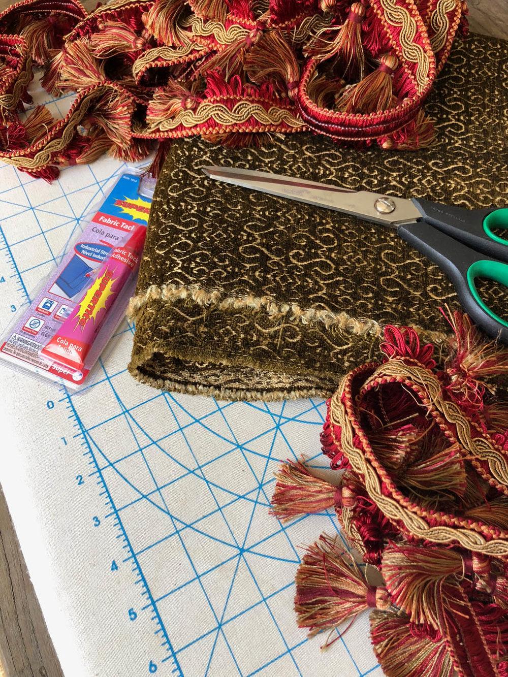 Reversible upholstery fabric glue, scissors, purchased fringe trim for making no-sew Christmas tree skirt.