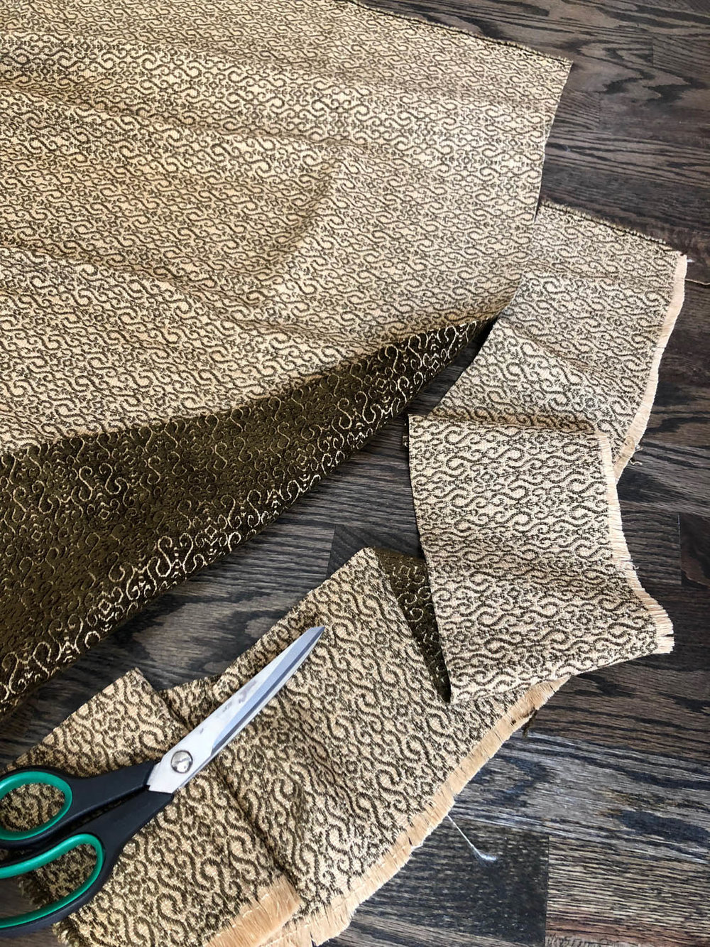 scissors cutting away edge of upholstery fabric