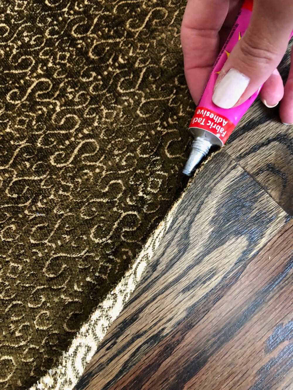applying super tite fabric glue to pressed under edges of upholstery fabric