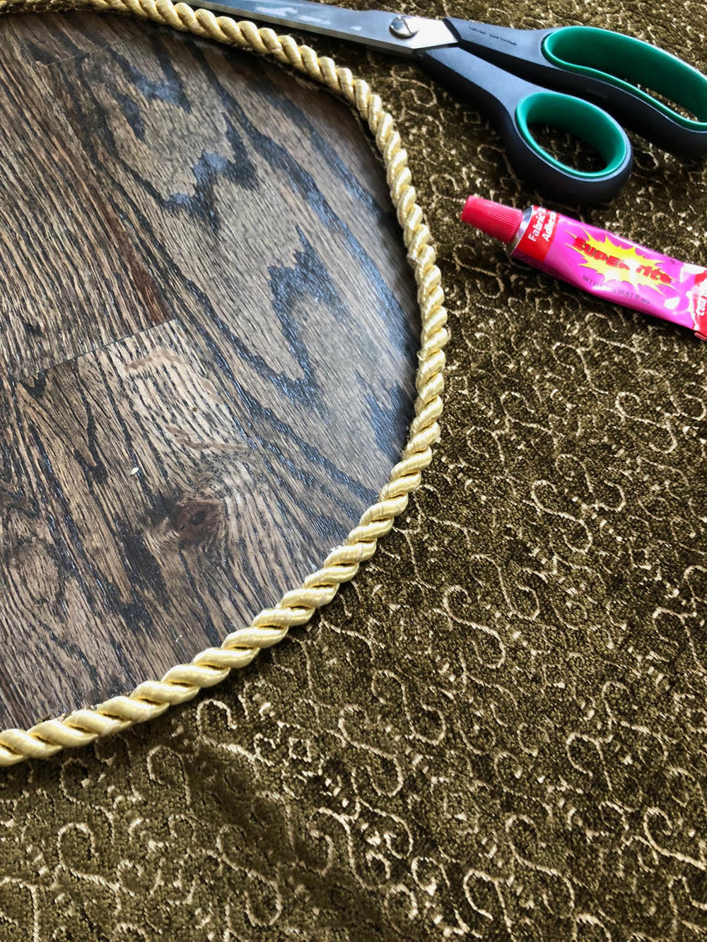 Using fabric glue to attach purchased rope trim to inner circle of reversible upholstery fabric on the Christmas tree skirt.