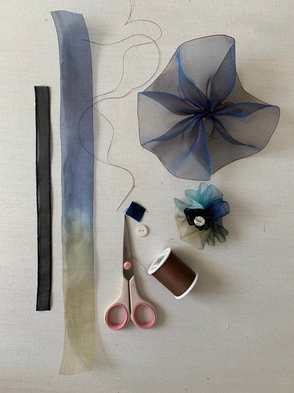 Black ribbon, variegated blue and green silk ribbon, scissors, needle with thread, spool of thread and finished Step by Step Simple Ribbon Flower for Embellishing