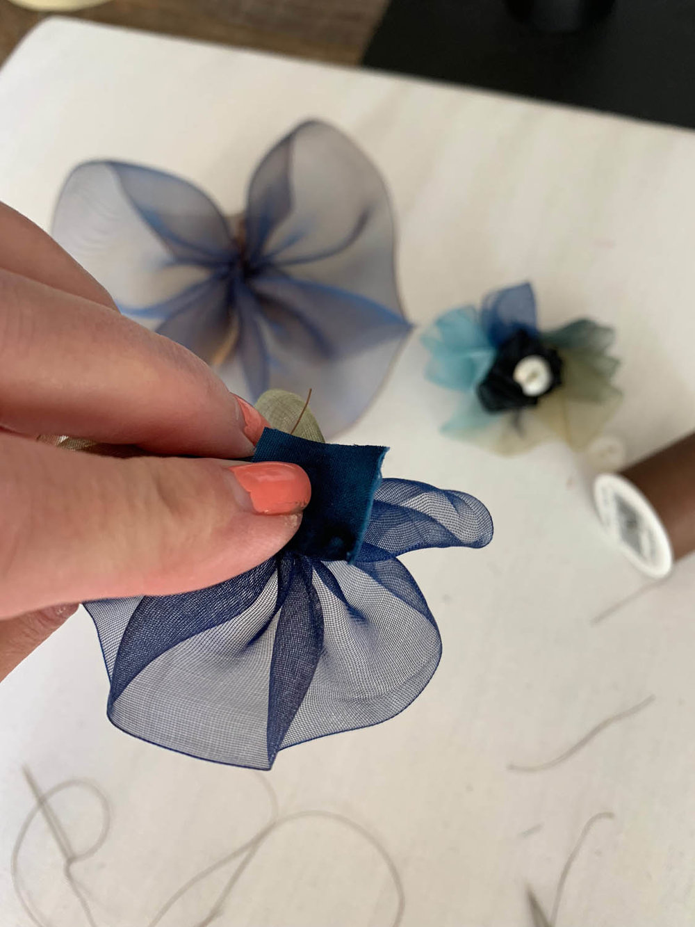 sewing square of fabric to center back of gathered ribbon