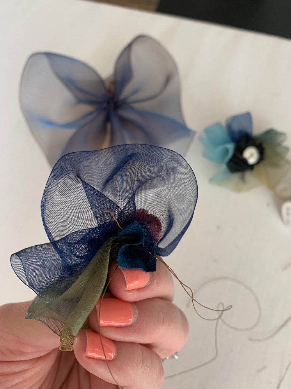 continuing to stitch small piece of fabric to back of gathered ribbon flower
