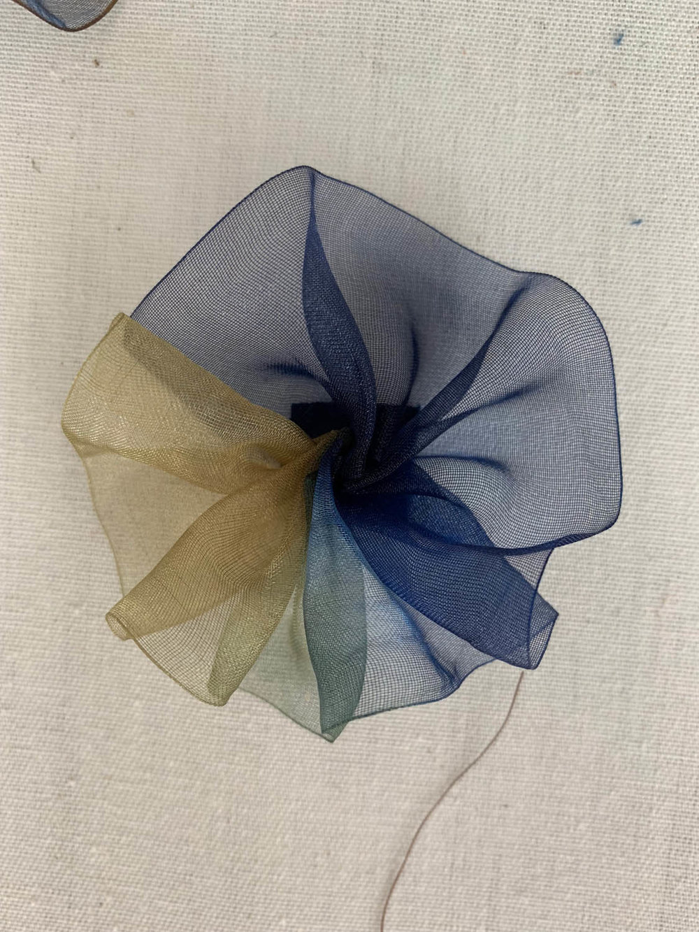 gathered variegated blue and green ribbon gathered together to make a silk ribbon flower for embellishments