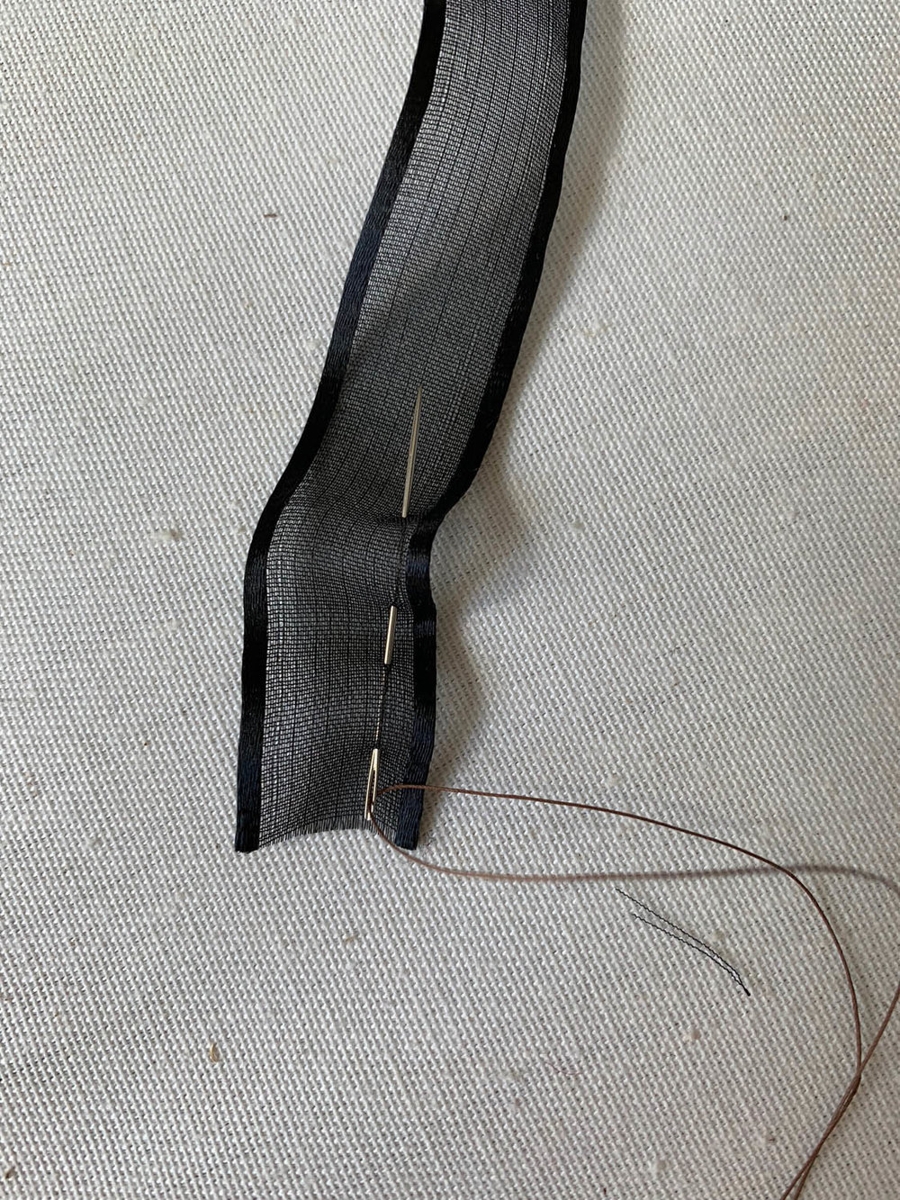 gathering black silk ribbon edge with needle and thread