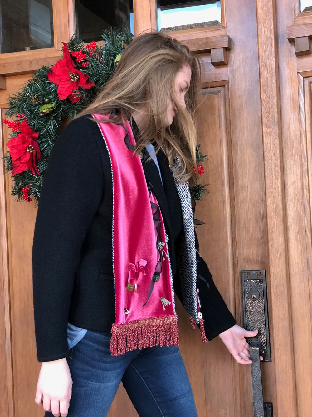 woman by door with Christmas wreath wearing red velvet embellished scarf