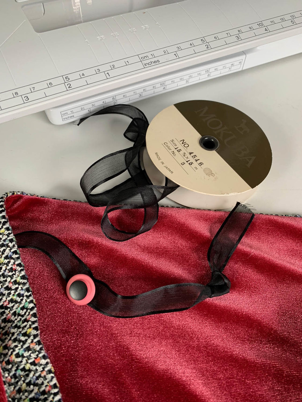 roll of black ribbon trim with red velvet scarf and sewing machine