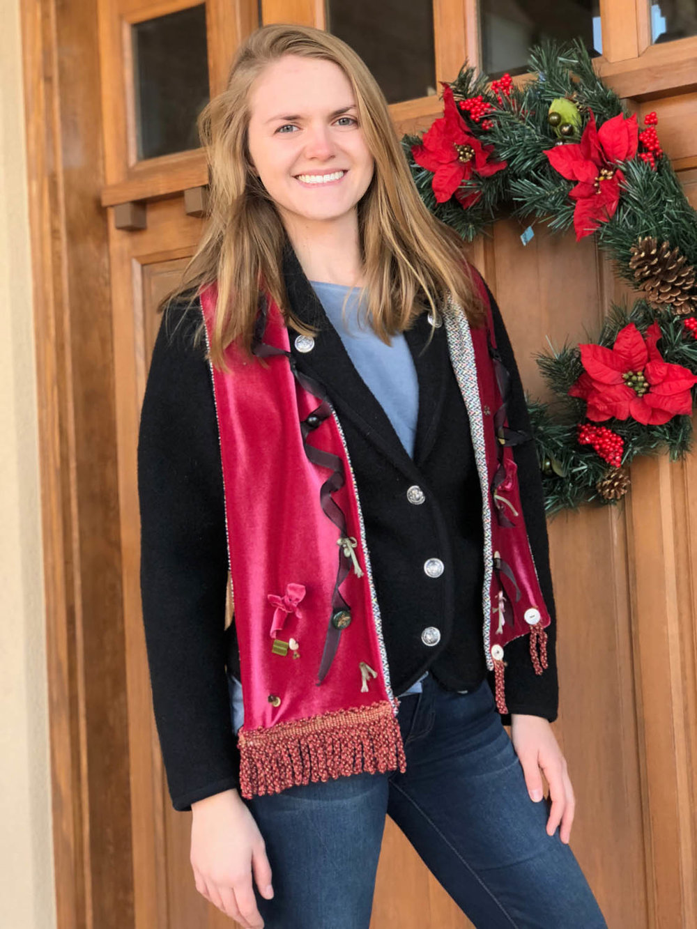 Woman wearing hand made velvet embellished winter scarf by wood door with holiday wreath.