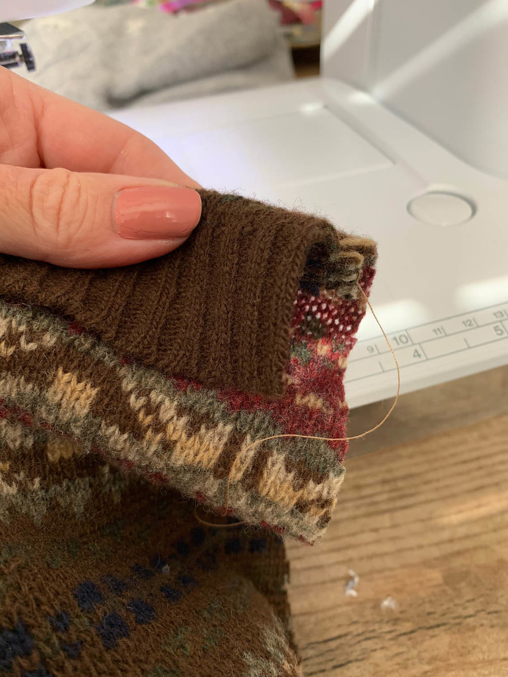 turning cuff of sweater to show front edge of stocking