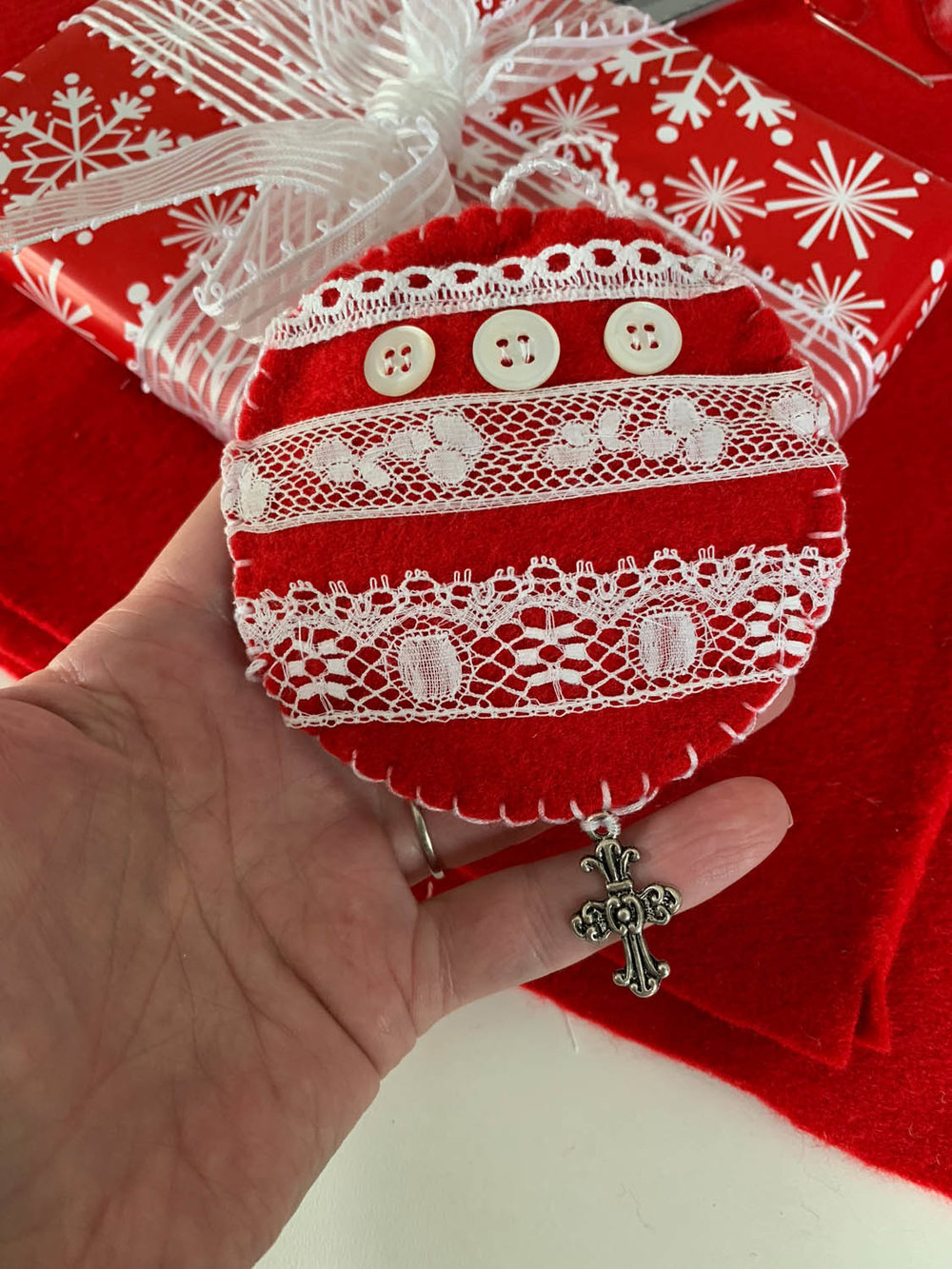 Red felt lace-embellished ornament decorating a gift wrapped box