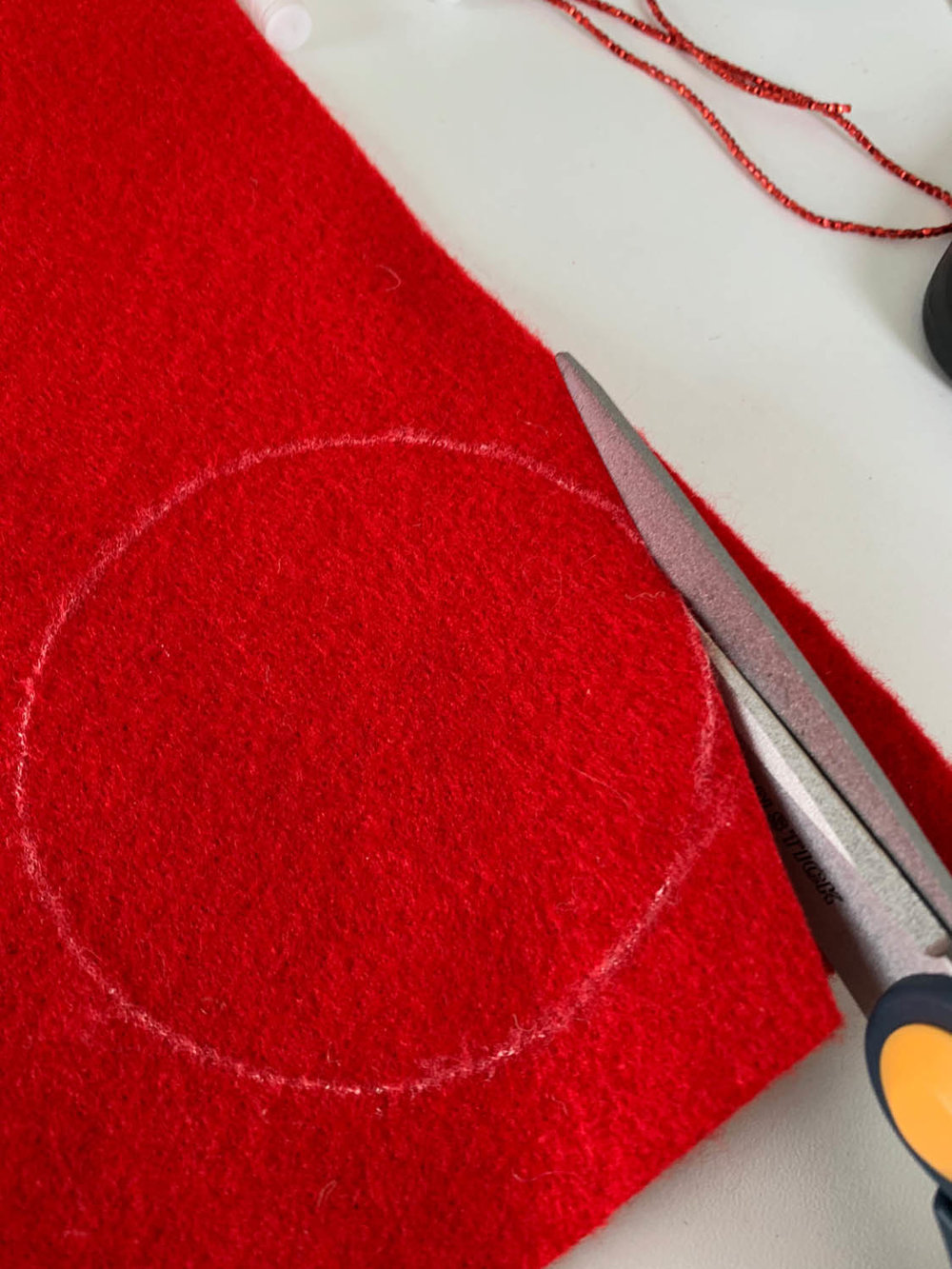 scissors cutting out traced circle shape on red felt