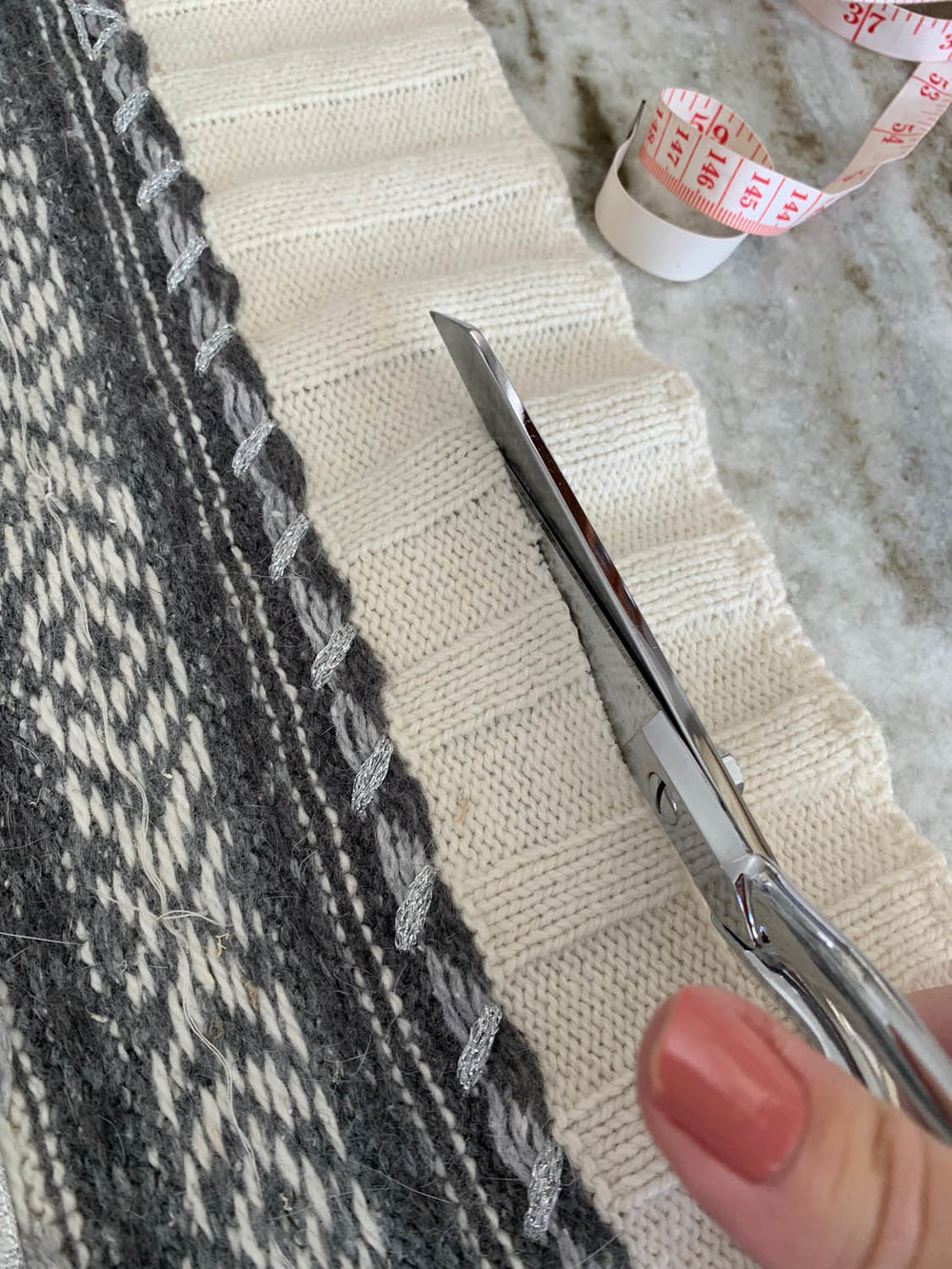scissors cutting bottom of sweater for upcycled pillow top