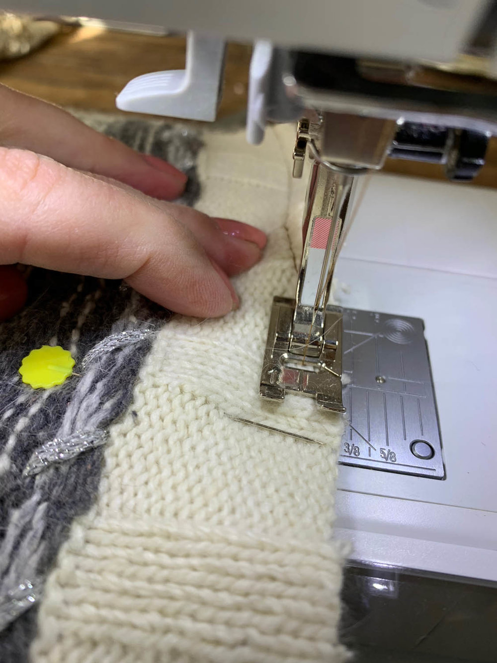 using sewing machine to stitch sweater pieces together for pillow