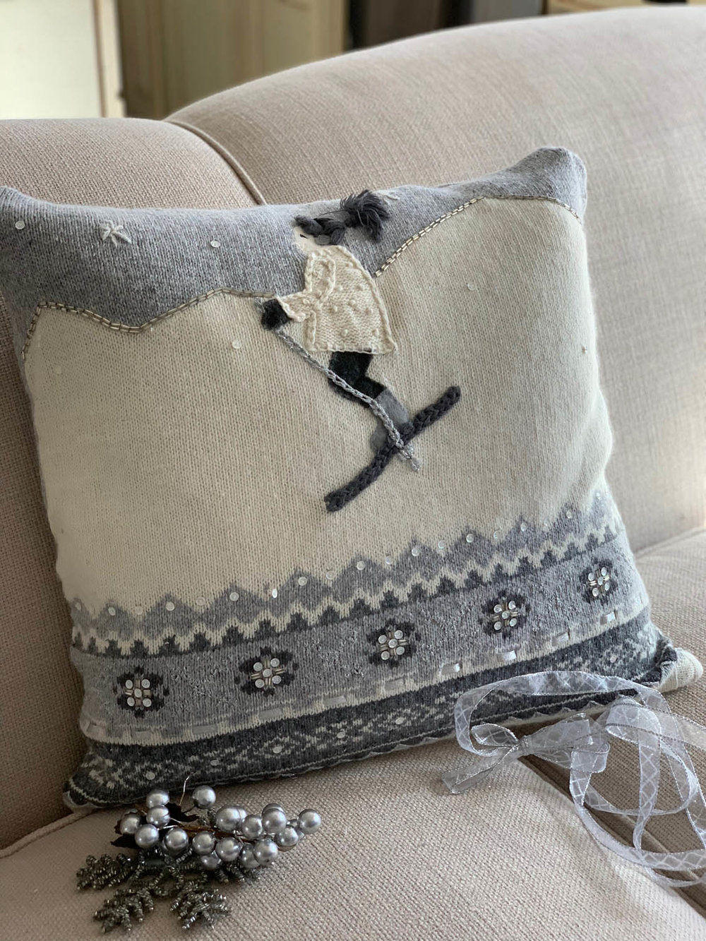 Finished thrift store knitted sweater in white and gray sewn into a holiday pillow.