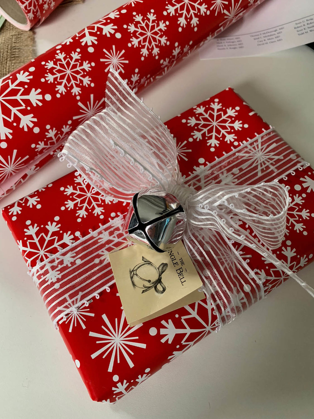 gift wrapped in read and white snowflake paper with white ribbon and jingle bell embellishment