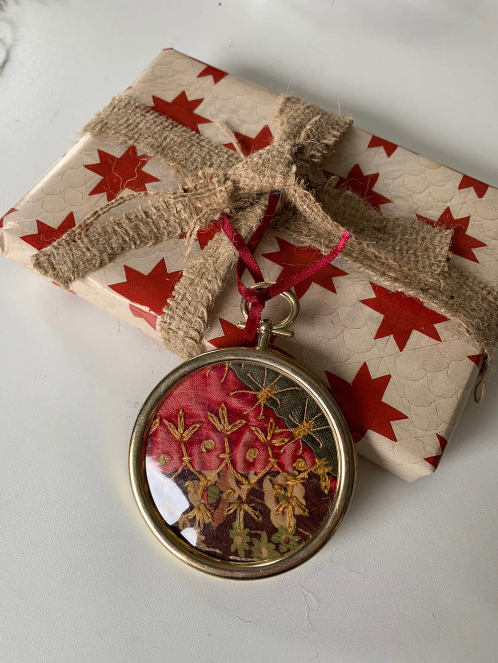 gift wrapped with burlap ribbon and ornament as embellishment