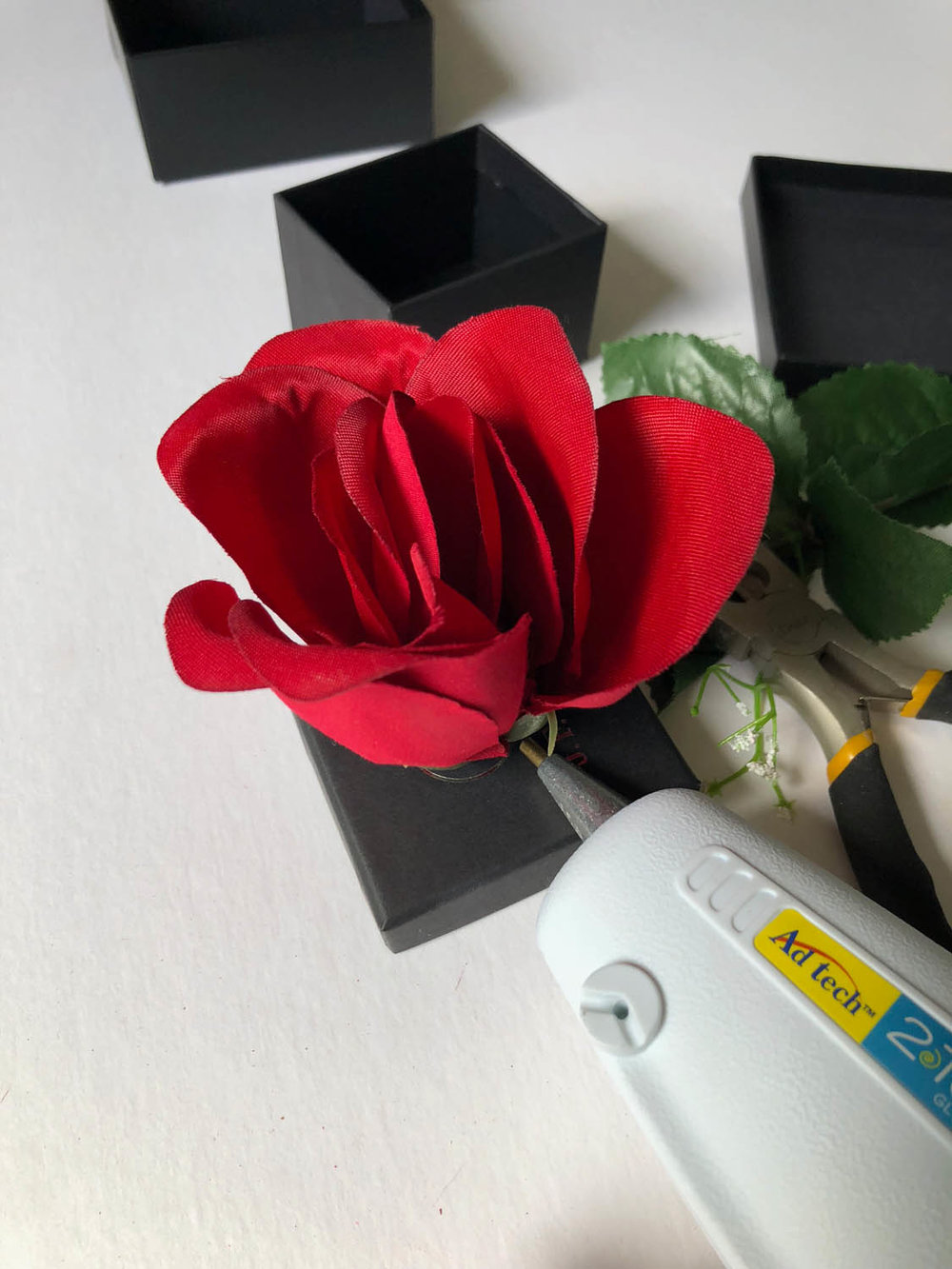 red silk rose pressed into top of small black gift box