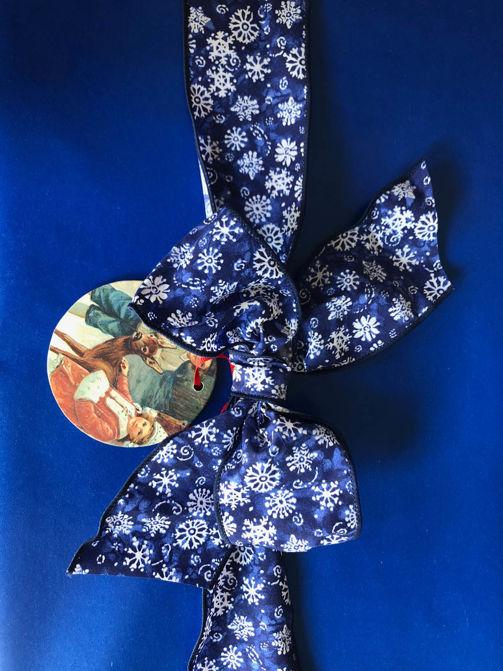 gift wrapped in blue with a ribbon and ornament attached