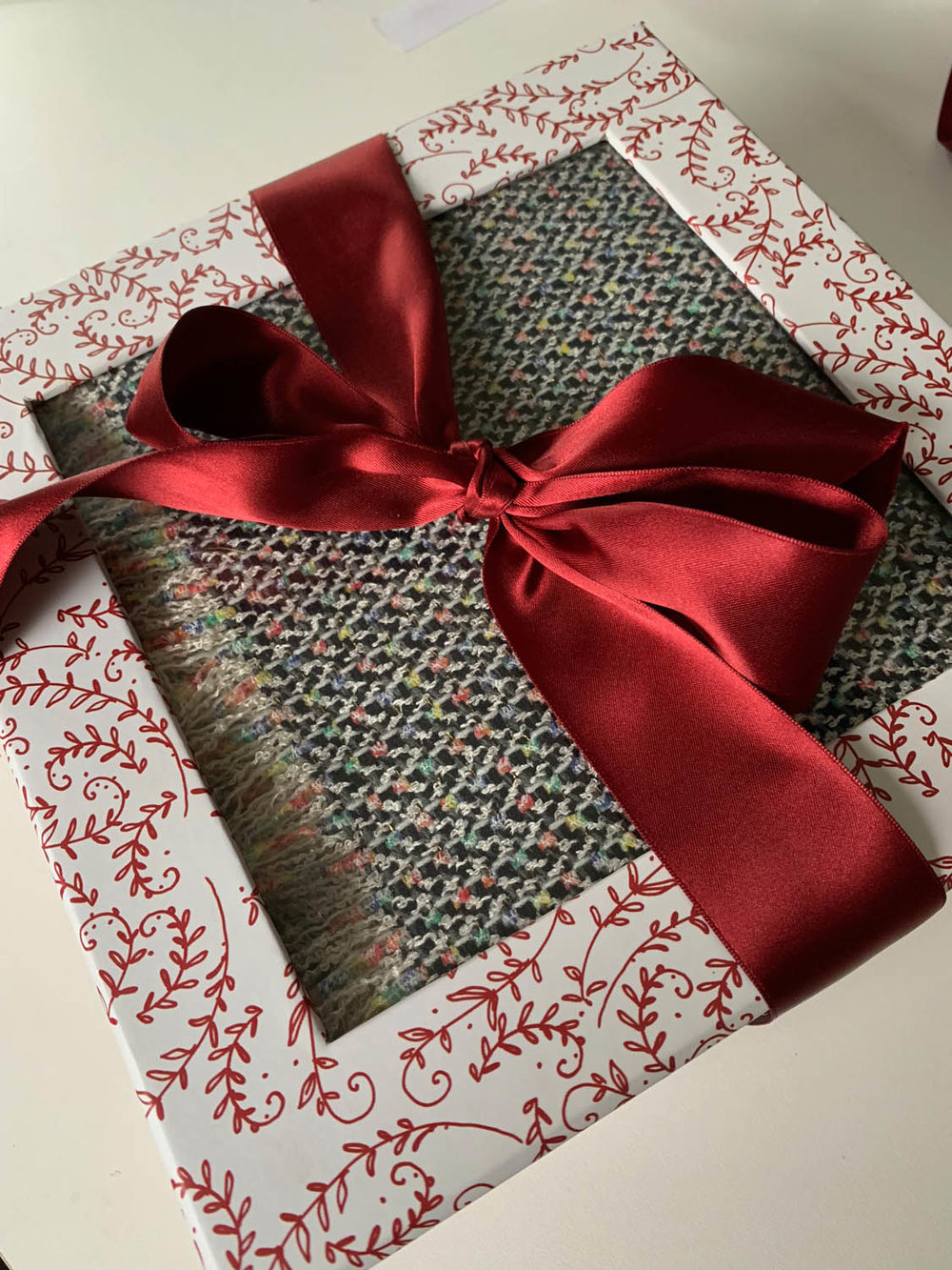 windowed gift box present embellished with a red ribbon