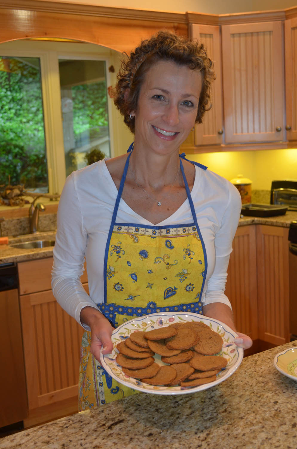 Ashley serving a plate of homemade chewy ginger cookies.