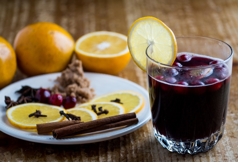 Mulled wine in a clear glass with floating berries garnished with an orange slice