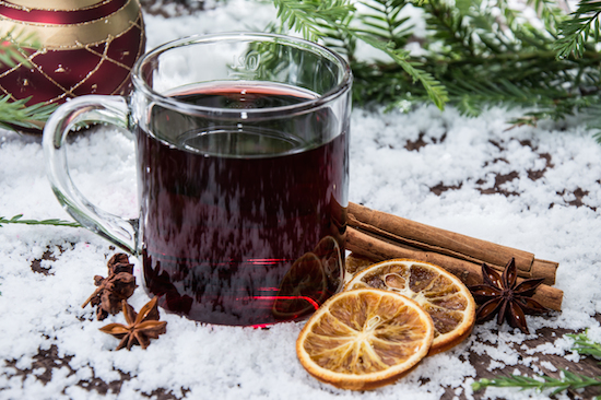 Mulled wine in a glass mug with cinnamon sticks and orange slices on snow.