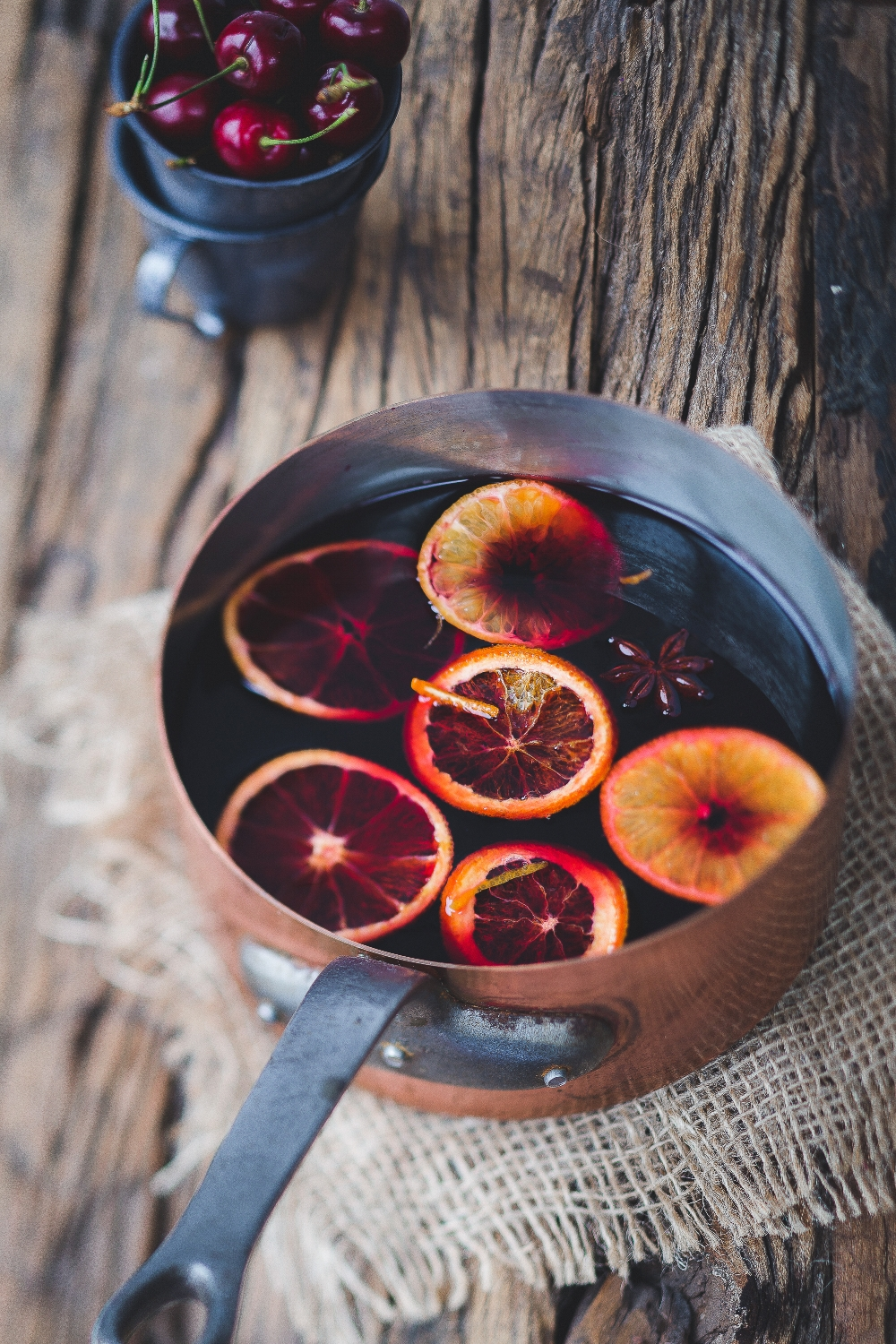 Orange slices atop mulled wine in a copper pot on a wooden table top.