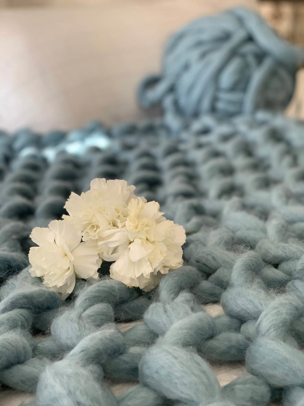 Finished 1-hour easy arm-knitted throw in dusty blue yarn with white hydrangeas