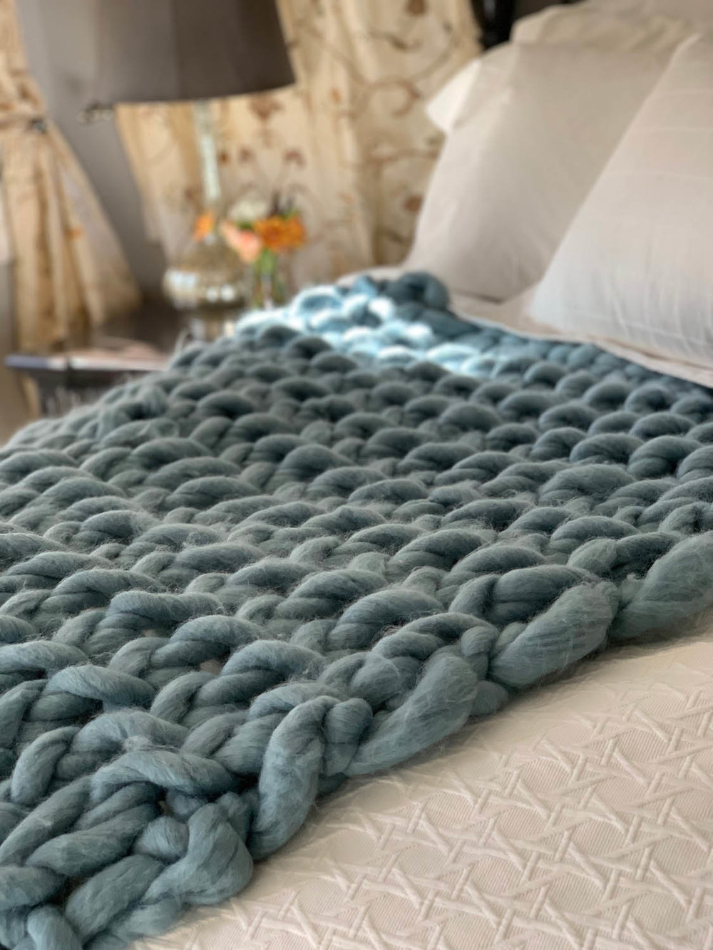 Finished 1-hour easy arm-knitted throw in dusty blue yarn