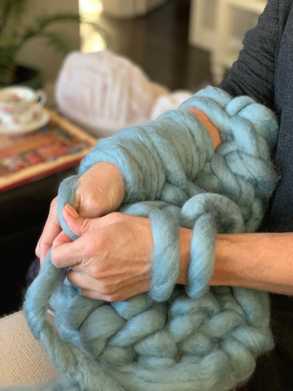 Making a single knit stitch on arms while making a 1-hour arm-knitted throw