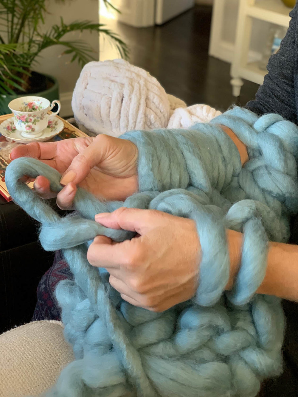 Rows of knitting on arms for making a 1-hour arm-knitted throw
