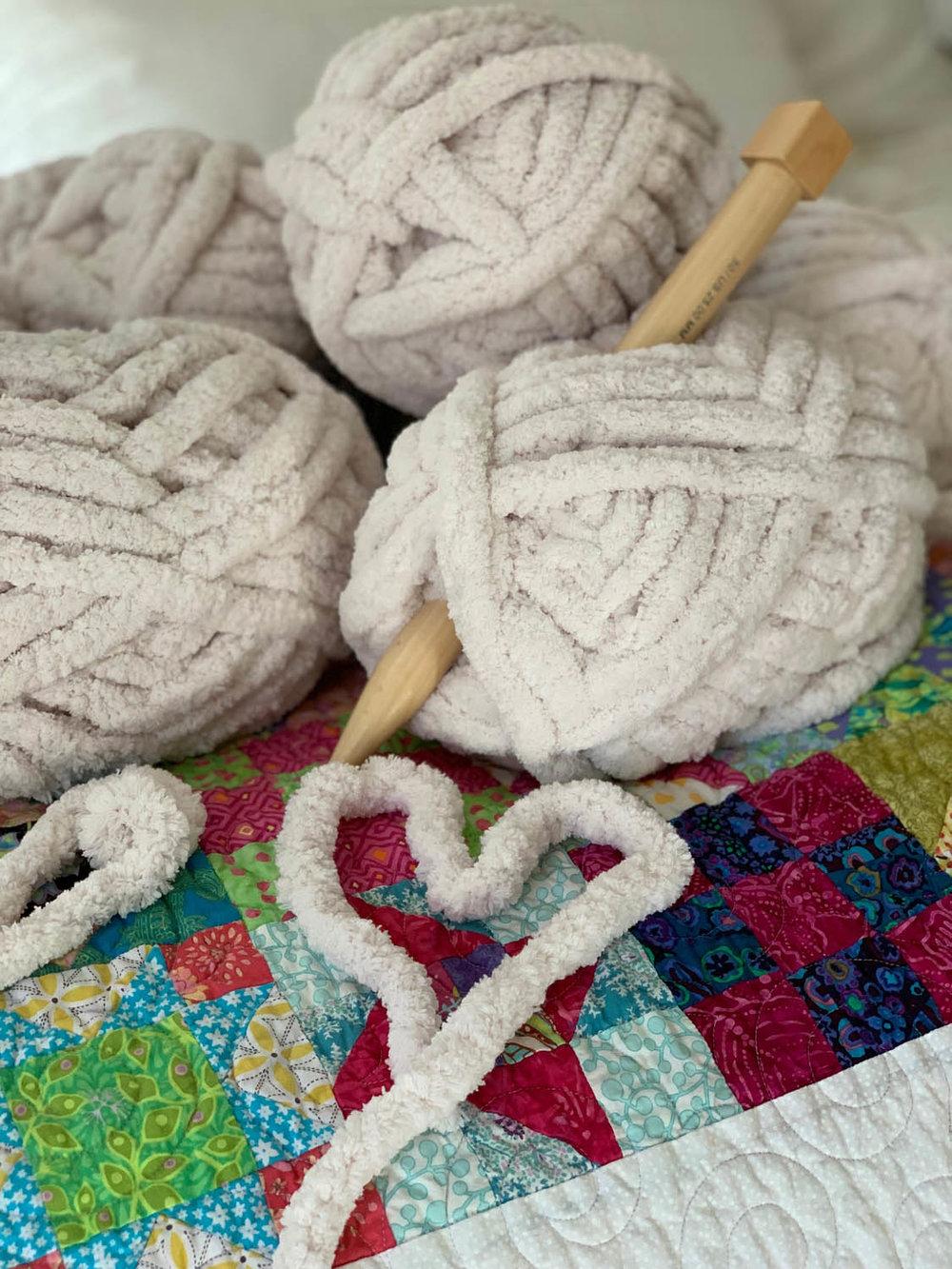 balls of bernat jumbo yarn on a quilt
