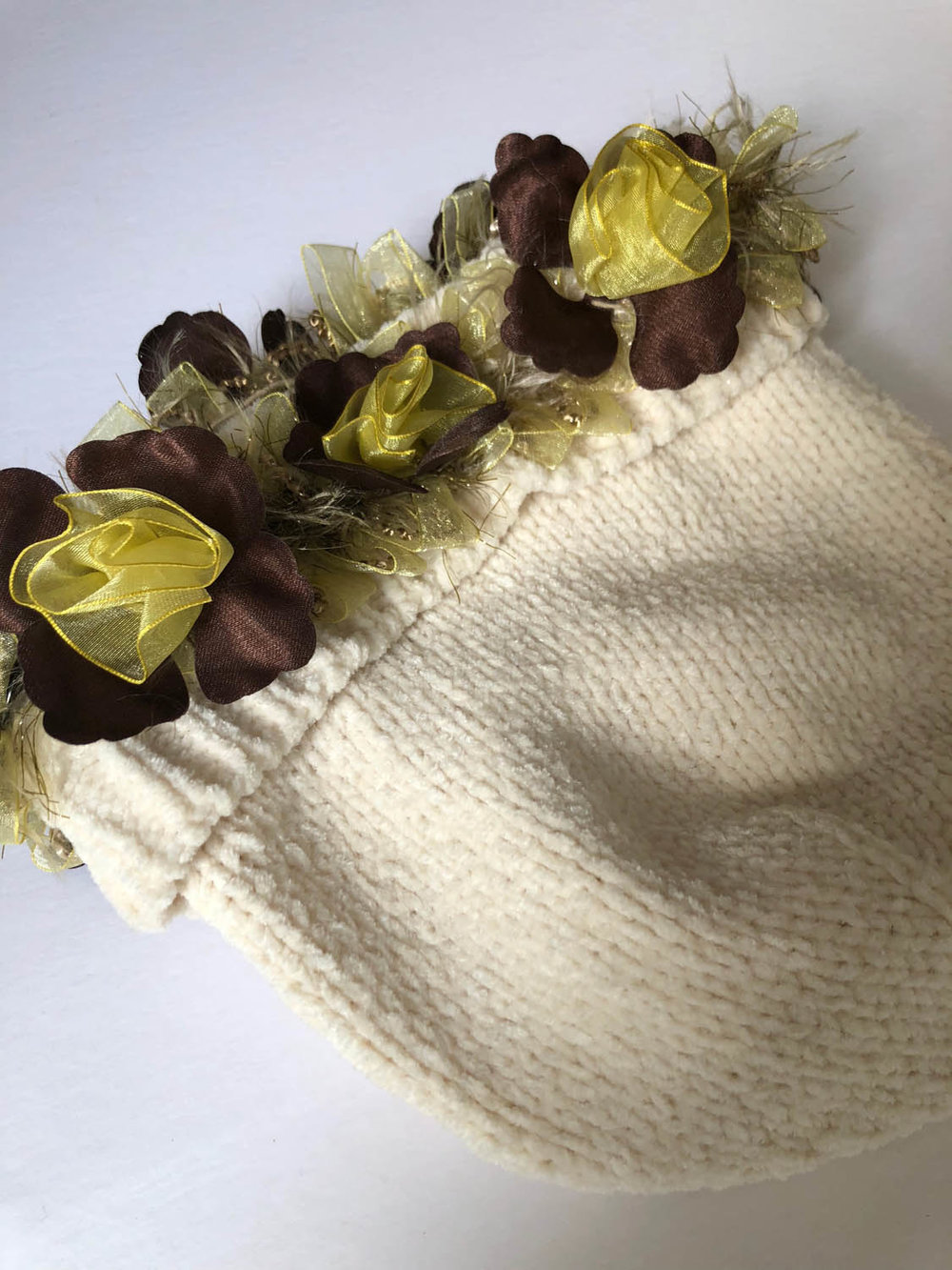 ribbon trim on an elastic band embellishes a white chenille winter hat