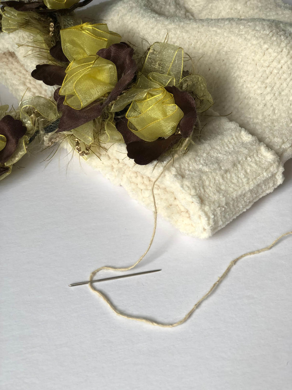 needle and thread sewing elastic trim to embellish a white chenille ladies winter hat