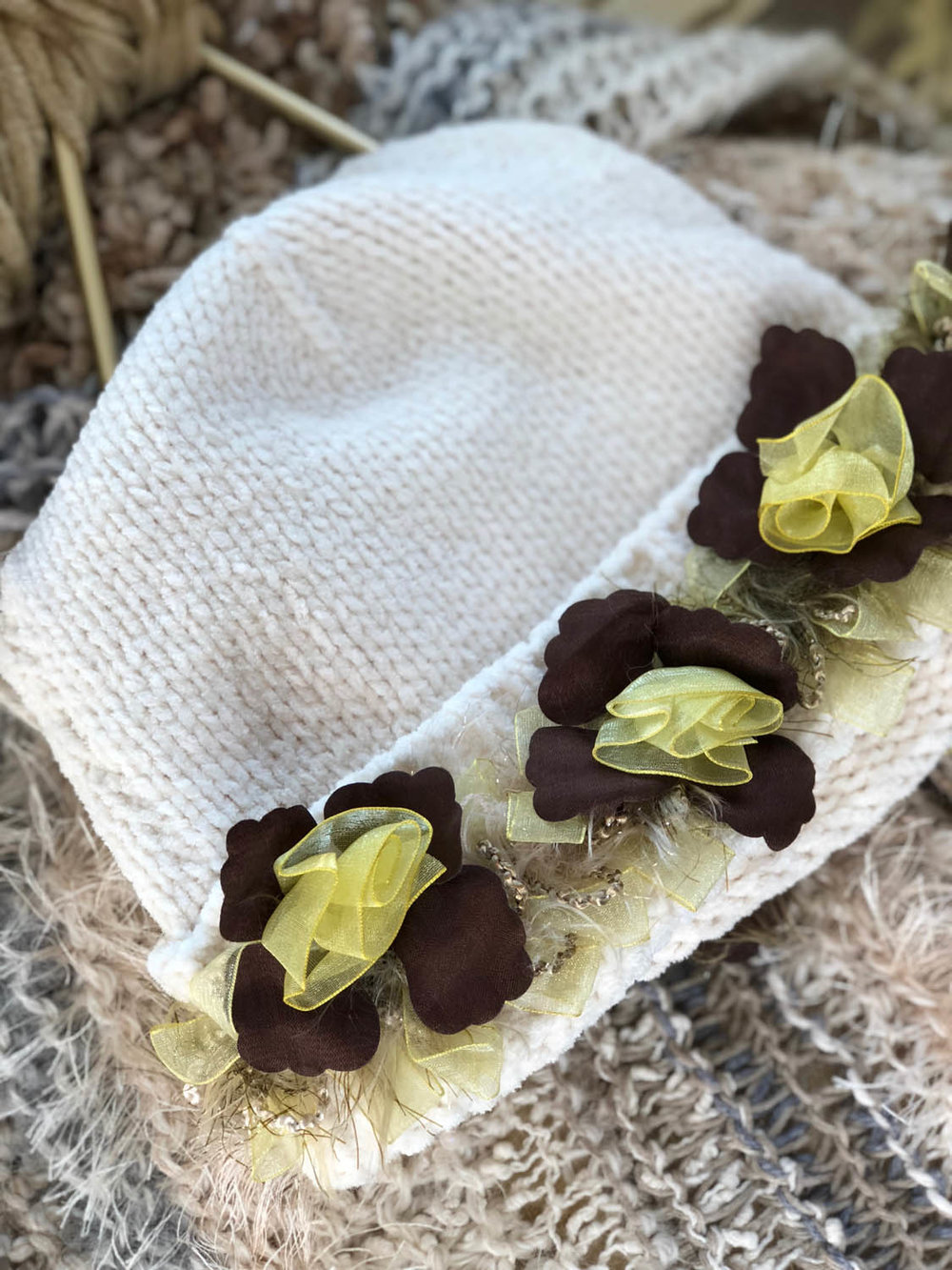 finished yellow ribbon rose trim embellishing a DIY white chenille women's winter hat