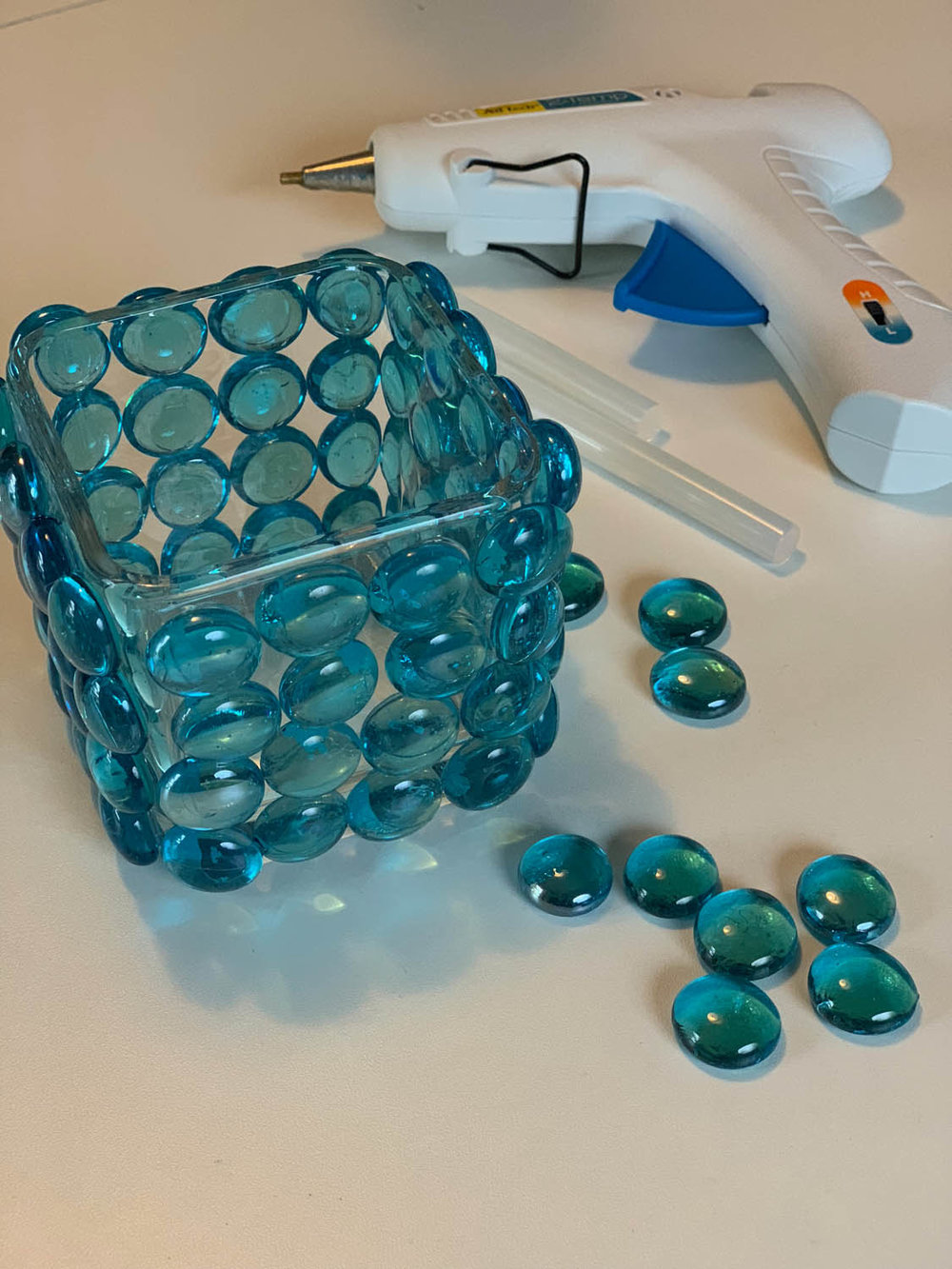 Decorative glass vase covered with blue marble beads with a glue gun